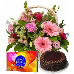 Beautiful Midnight Gift of Cadbury Celebration Pack with Seasonal Flowers Basket and Delicious Chocolate Cake