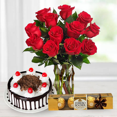 Glorious 12 Red Roses along with toothsome 1 lb Black Forest Cake and 4 Pcs. crunchy Ferrero Rocher Chocolates gift hamper